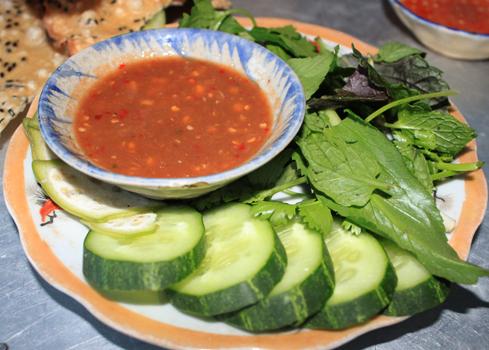 Ăn kèm là chén nước chấm cùng các loại rau như chuối chát, dưa leo, khế, ngò gai...
