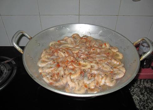 Tôm sau khi ướp gia vị được cho lên chảo luộc chín.