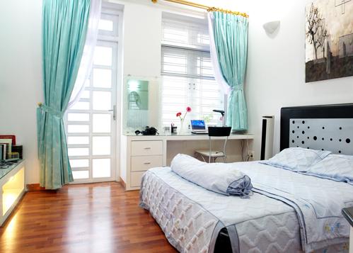 Không gian phòng ngủ vừa đủ, không mất đi sự cân đối. Các bàn học và kệ ti vi đều làm bằng bê tông ốp gỗ.