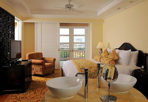 Sự kết hợp động điệu giữa các họa tiết hoa văn cùng tông màu trắng, vàng nhạt tôn vẻ mềm mại, ấm áp cho phòng ngủ. Hệ tủ kệ thiết kế theo kiến trúc Đông Dương làm điểm nhần cho căn phòng thêm sang trọng, lịch lãm hơn. Ảnh:Danangtourism.