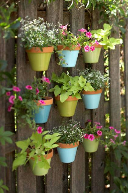 Hàng rào hoặc bức tường tẻ nhạt của nhà bạn sẽ có thêm màu sắc nhờ gắn  thêm những bình hoa nhiều màu.