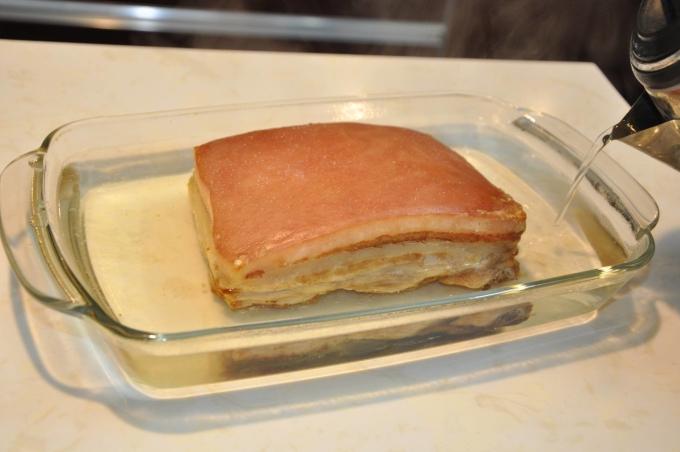"""<p class=""""Normal""""> Rót nước sôi ngập 1/2 miếng thịt (tuyệt đối không được rót nước lên bì). Cách làm này giúp cho miếng thịt mềm, ngọt đúng vị của thịt, chín đều và không bị khô.</p> <p class=""""Normal""""> Người Anh thường làm đơn giản mà vẫn thơm ngọt đúng mùi vị của thịt. Còn nếu bạn muốn tẩm ướp theo kiểu người Việt thì hãy cho toàn bộ gia vị nhưngũ vị hương, đường, hạt tiêu, tỏi, ớt...vào nồi nước rồi đun sôi lên, cho nước này vào khay thịt thay cho nước đun sôi như hình. Món thịt sẽ mềm và ngấm gia vị như bạn mong muốn. Khi làm xong, phần nước này có thể cất tủ đông để lần sau lại đun sôi đổ vào tiếp cho đỡ mất thời gian.</p>"""