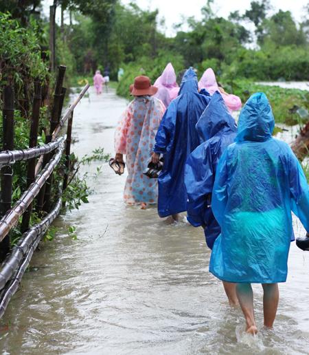 Cả đoàn nhà trai mặc áo mưa, lội nước hơn 500m để vào nhà cô dâu, vì xe ô tô không thể vào trong được nữa.