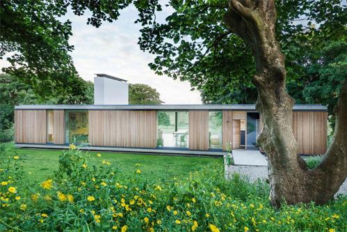 Ngôi nhà ở thị trấn Swanage (Anh) của gia chủ tới tuổi nghỉ hưu. Công trình một tầng hiện đại nằm hài hòa giữa những cây cổ thụ tán rộng.