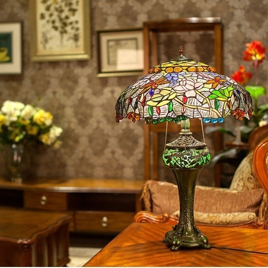 Đèn chuồn chuồn hoa sen lấy tông chủ đạo là màu xanh lá từ chao đèn đến chân đèn. Đèn Tiffany được chạm trổ hình những bông sen hồng xen kẽ tán lá xanh, điểm xuyết thêm những viên đá sắc màu tạo điểm nhấn nổi bật. Chao đèn được làm thủ công bằng cách hàn ghép từng miếng kính màu, tạo nên những chiếc đèn độc đáo mang đường nét riêng. Đèn Tiffany cao 49 cm, thích hợp đặt tại phòng ngủ, sảnh, phòng khách...