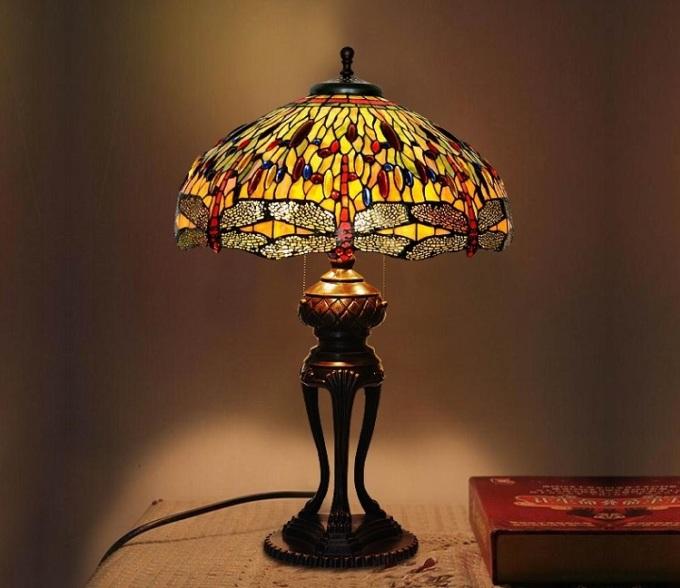 Đèn chuồn chuồn mang sắc vàng ấm áp, cho ánh sáng dịu nhẹ, thích hợp với không gian phòng ngủ. Chao đèn được lắp ghép thủ công tỉ mỉ từ những mảnh thủy tinh Tiffany màu. Chân đèn làm bằng chất liệu thép chắc chắn, được xử lý bề mặt màu đồng cổ, chạm trổ hoa văn tinh xảo. Sản phẩm sử dụng bóng đèn Led thế hệ mới, có khả tiết kiệm điện đến 90% so với bóng đèn thông thường.