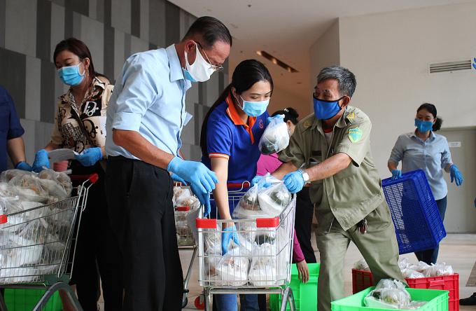 Ngày hai bữa, lãnh đạo, dân quân và tình nguyện viên phường 1 , quận 4, tập trung lại giao cơm cho cư dân. Ảnh: Diệp Phan.