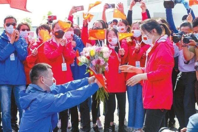 Anh Hu cầu hôn bạn gái trước sự chứng kiến của đông đảo đồng nghiệp, cấp trên. Ảnh: Chinanews.