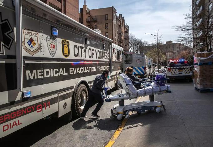 Một nhân viên y tế đẩy bệnh nhân nhiễm Covid-19 nhập viện từ chiếc xe buýt chuyên dụng. Ảnh:David Dee Delgado/Bloomberg.
