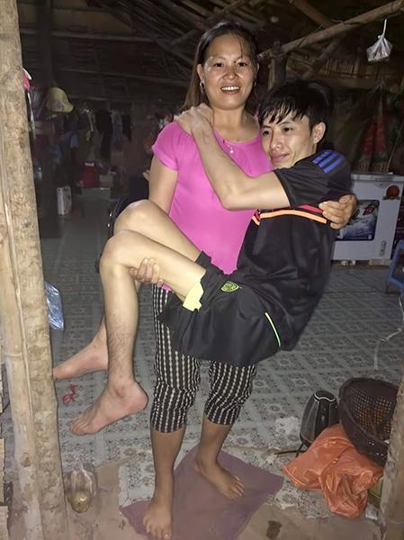 Chồng bị liệt hai chân, năm đầu tiên, chị Bùi Thị Hoa thường phải bế chồng phục vụ sinh hoạt cá nhân. Ảnh:Nhân vật cung cấp.