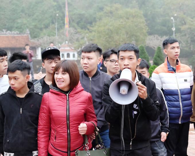 Tiến Đạt (cầm loa) àm quản trò trong chuyến du xuân của trường Nguyễn Văn Tố khi thực tập tại công ty du lịch năm 2018. Ảnh: Nhân vật cung cấp.
