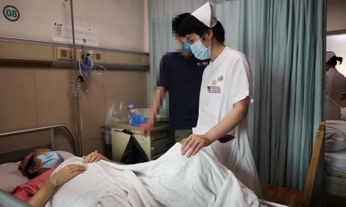 Bác sĩ Lưu Ngọc Binh của Bệnh viện phụ sản Quảng Châu, Trung Quốc thăm hỏi Vương Lệ sau khi sinh đứa con thứ hai sau 24 ngày trì hoãn. Ảnh: sina.