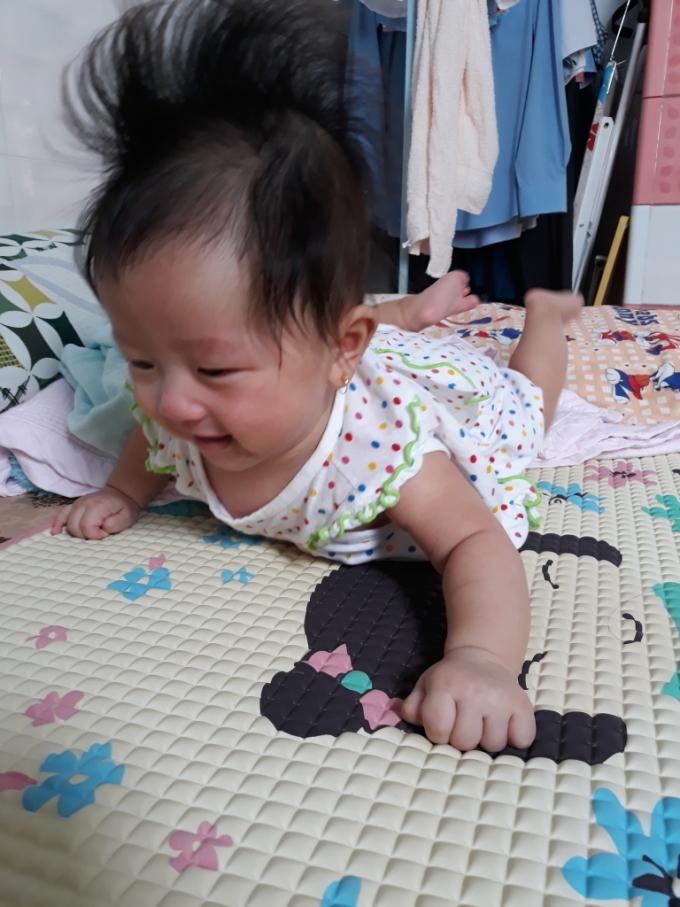 Bé Cơm đang cố gắng tập lật và cái lật hoàn hảo đầu tiên không nhờ vào sự giúp sức của bất kỳ ai lúc 4 tháng tuổi. Khi lật thành công, mái tóc của con cũng dựng thẳng đứng vừa thấy đáng yêu vừa buồn cười.