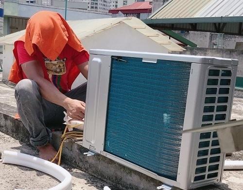 Thợ điều hòa lắp đặt cục nóng ngoài trời. Những ngày cao điểm, các đội thợ thường chọn lắp đặt, để có thu nhập cao, thay vì chỉ sửa chữa hay bơm khí gas. Ảnh: Vũ Xuân.