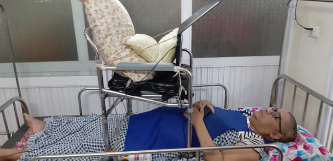 Khi chưa thể ngồi xe lăn, bố mẹ anh Tuấn thiết kế bàn treo laptop để con có thể nằm làm việc. Ảnh: Nhân vật cung cấp.