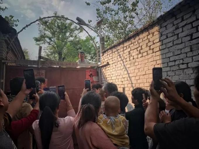 Dân làng Châu Lâu đứng trước cổng nhà Chu Chí Văn mỗi ngày để xin tiền, vay tiền hoặc làm livestream kiếm tiền. Ảnh: sina.