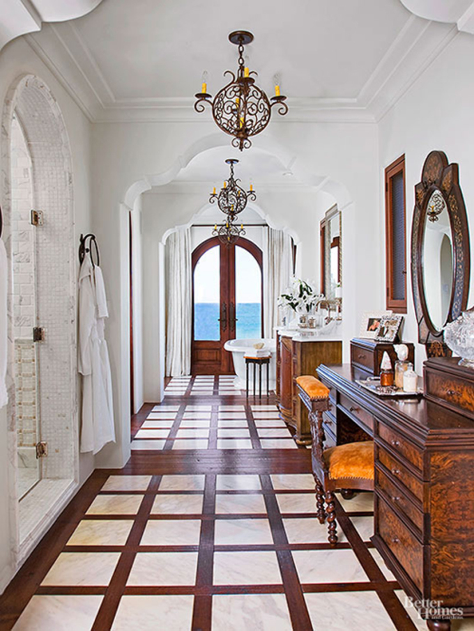 Với diện tích phòng tắm thiên về chiều dài, nhà tắm tạo điểm nhấn với sơn màu trắng, kết hợp với nội thất đồ gỗ. Không gian gây chú ý với cửa hình vòm rộng, giúp gia chủ ngắm nhìn cảnh sắc thiên nhiên. Thiết kế cũng khéo léo phân không gian thành các khu vực để bồn tắm, chậu rửa, bố trí gương...