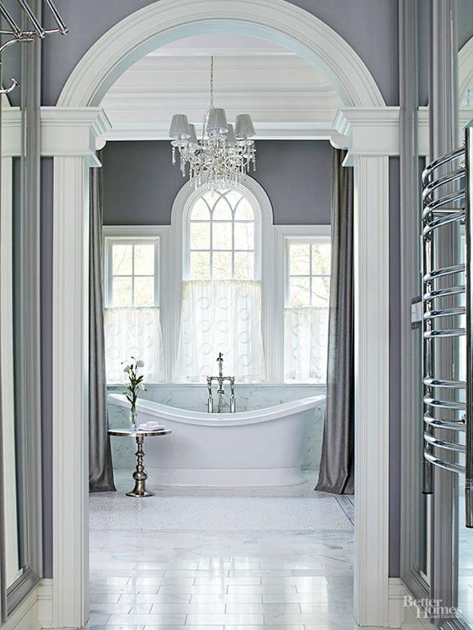 Phòng tắm sơn màu trắng, lắp đèn chùm sang trọng. Không gian ấn tượng với cửa vòm lớn, gia chủ khéo léo bố ba cửa sổ đồng bộ giúp đón ánh sáng tự nhiên.