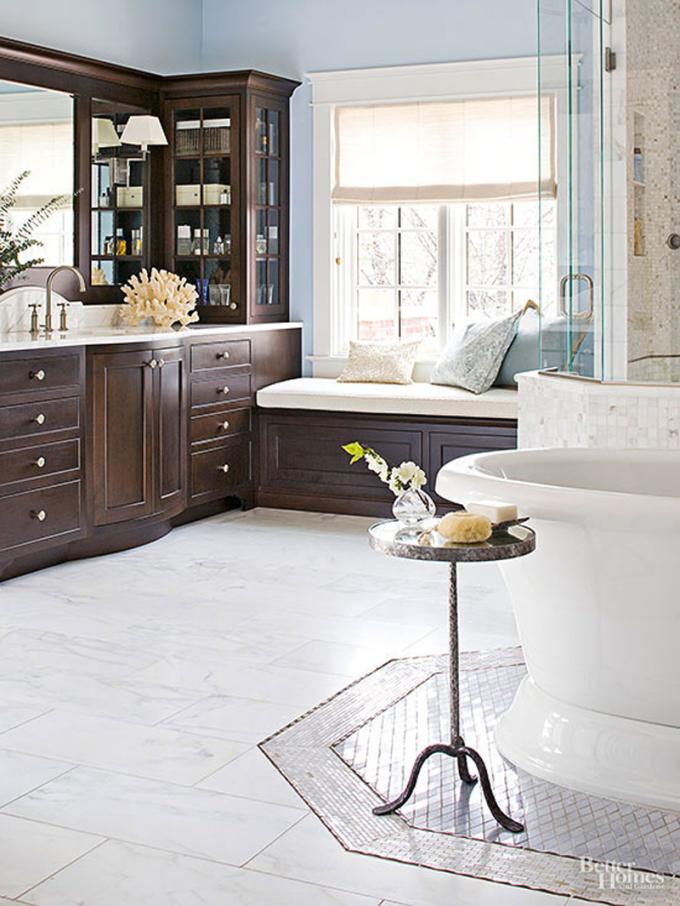 Những viên gạch nền màu trắng được sắp xếp cẩn thận, vị trí đặt bồn tắm lắp gạch màu tối hơn, phân biệt các khu vực. Trong phòng, bàn trang điểm, tủ trưng bày đặt bên cạnh. Bên cạnh khung sửa sổ lớn, gia chủ bố trí thêm ghế ngồi, giúp thư giãn.