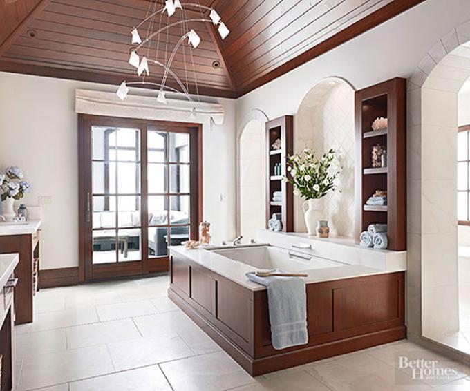 Trần nhà, bồn tắm ốp gỗ tạo điểm nhấn cho không gian. Gia chủ bố trí thêm kệ để đổ, tủ âm tường... thuận lợi để đồ dùng như quần áo, khăn tắm.