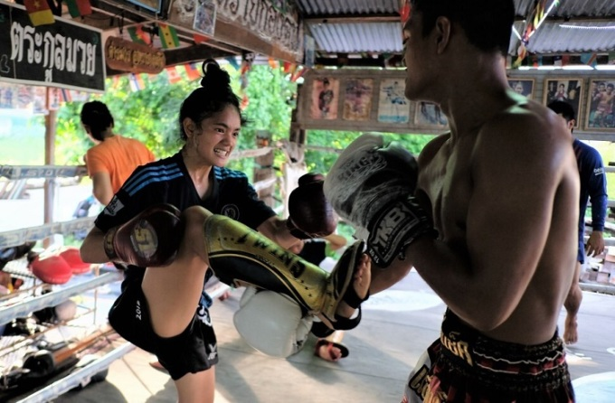 Kullanat Yoohanngoh (trái), một học sinh trung học 18 tuổi, là một võ sĩ Muay Thái chuyên nghiệp, tập luyện cùng anh trai Phoobadin tại phòng tập thể dục của cha họ ở Bangkok. Ảnh: Tibor Krausz.
