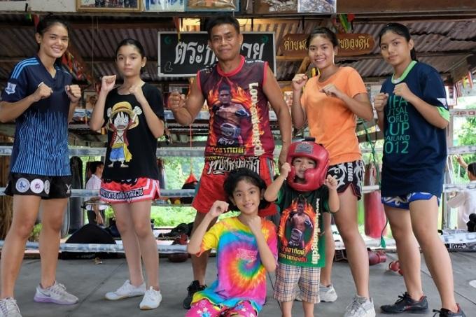 Nopparit Yoohanngoh, người đã đào tạo tất cả 16 đứa con của mình ở Muay Thai, chụp cùng với năm cô con gái và một đứa cháu tại phòng tập thể dục nhỏ của mình ở Bangkok. Ảnh: Tibor Krausz.