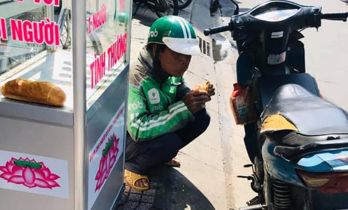Ông Hải với chiếc xe cũ, yên rách nát và chai dầu nhớt thường ghé ăn bánh mỳ tình thương của chị Loan mỗi ngày. Ảnh: Ngọc Loan.