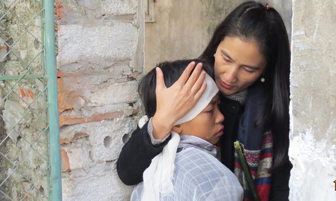 Chị Vũ Thị Dung ôm cậu bé Đàm Quyết Thắng ở Đồng Văn, Hà Nam trong tang lễ của mẹ năm 2017. Bố mẹ và em của Thắng đều mất vì HIV. Trước khi vào Khát Vọng, cậu bé 13 tuổi khi đó bị suy nhược và trầm cảm nặng, không dám gặp ai do bị kỳ thị. Hiện nay, Thắng đã vào lớp 10, rất tự tin, có thể đóng được hài kịch. Ảnh: Nhân vật cung cấp.