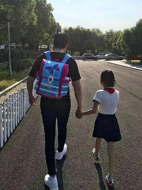 Nhiều phụ huynh Trung Quốc phải đeo cặp cho con khi đến trường. Ảnh: QQ.