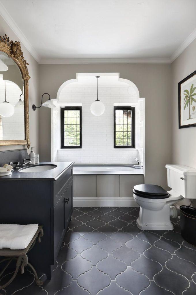 Trong ảnh, vị trí của các cửa sổ khung đen góp phần tạo nên sự cân bằng đối xứng cho phòng tắm, giúp đón ánh sáng mặt trời. Đèn treo tường, gạch lát sàn kiểu đen mang đến cho không gian nét truyền thống. Cuối cùng, một chiếc gương khung màu vàng giúp căn phòng trở nên sang trọng.