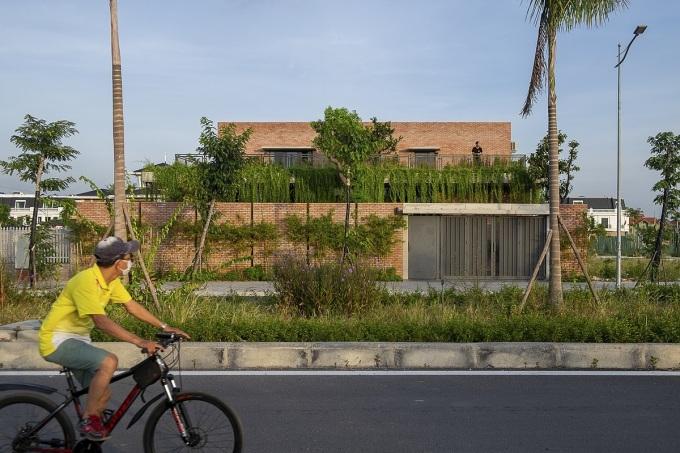 Nhìn từ bên ngoài, ngôi nhà nổi bật với màu đỏ của gạch và màu xanh của cây cối. Ảnh: Đức Nguyễn.