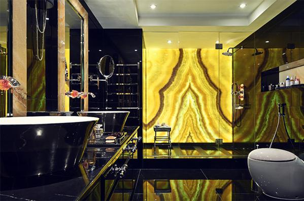 Nhìn từ ngoài vào, phòng tắm như một bức tranh bằng lụa với màu vàng là điểm nhấn. Một phần gạch ốp tường, sàn nhà màu đen giúp tôn thêm sắc vàng. Gia chủ bố trí cửa ngăn cách các khu vực bằng kính giúp căn phòng thông thoáng, sang trọng.