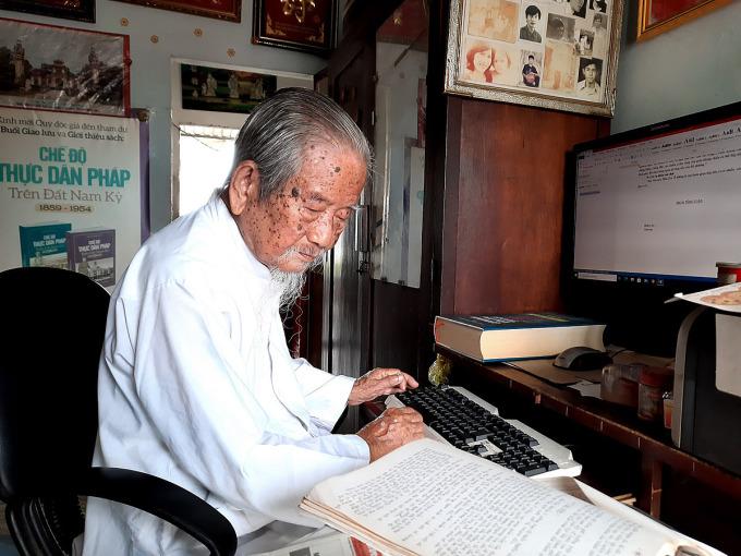 Cụ Tư đang chép lại bản thảo cuốn sách về lịch sử thành phố Hồ Chí Minh viết bằng máy đánh chữ của mình 22 năm trước vào máy vi tính, chỉnh sửa, bổ sung để gửi nhà xuất bản. Ảnh: Diệp Phan.