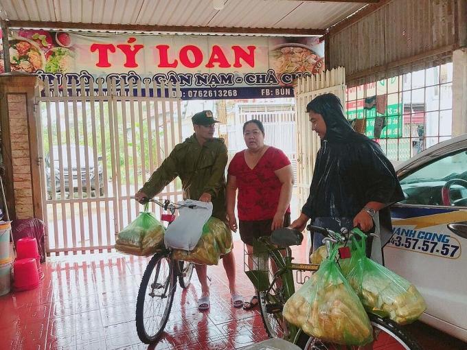 Chị Loan giao bánh mì cho cán bộ phường và anh Phong nhờ vận chuyển đến bà con đang bị cô lập ở Cồn Hến, phường Vỹ Dạ. Ảnh: Ngọc Loan.