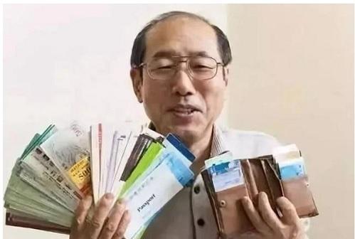 Ông Tongya Hiroshi khoe những tờ phiếu giảm giá trong ví của mình. Ảnh: Sinchew.