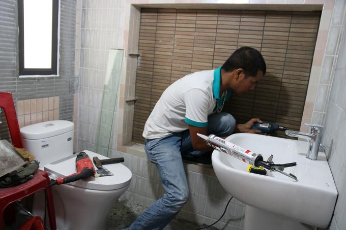 Ekip chương trình sử dụng chất liệu chống thấm, chống trơn khi cải tạo phòng tắm. Ảnh: Giang Chinh.
