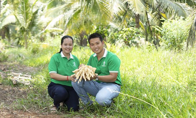 Hai vợ chồng Thạch Thị Chal Thi và Phạm Đình Ngãi bên vườn dừa lấy mật của gia đình. Ảnh: Nhân vật cung cấp.
