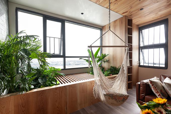 Góc vườn trong căn hộ vớ cây xanh, sàn gỗ và võng. Ảnh: H2.