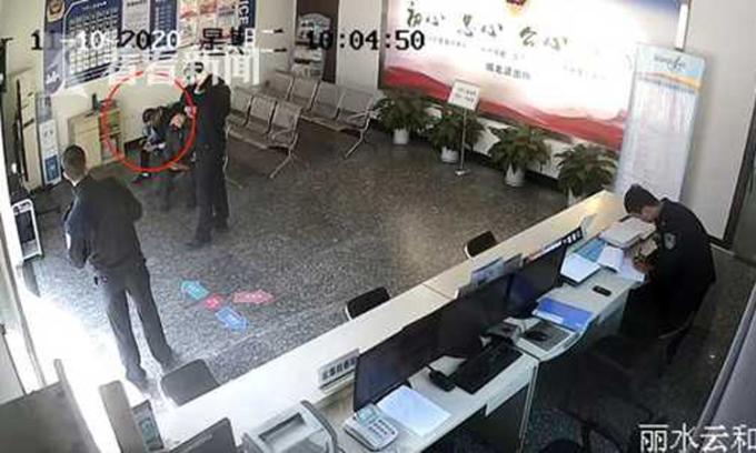 Mã (khoang đỏ) ngồi chờ người chủ trọ làm giấy tờ tại sở cảnh sát địa phương. Sau đó người đàn ông này bị phát hiện chính là tên trộm đang bị truy tìm. Ảnh: kknews.