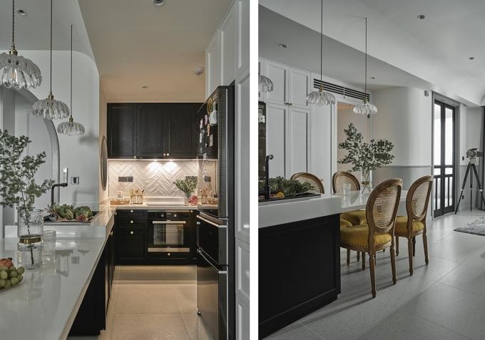 Tủ bếp được sơn đen và nối dài, gắn liền với bàn ăn. Cửa toilet được sơn trắng nên nhìn từ xa trông như một cánh tủ. Ảnh: Đỗ Sỹ.