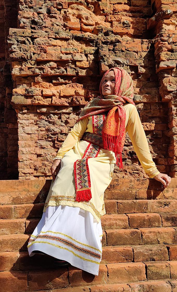 Bà Hoàng được con trai thuê trang phục, hướng dẫn tạo dáng chụp hình tại tháp Chăm Poshanư. Ảnh: Tấn Thanh.