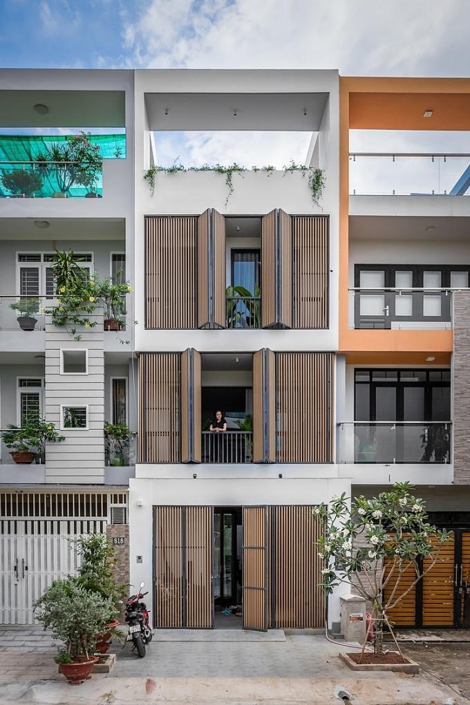Mặt đứng được thiết kế với những lam và cửa xếp có thể đóng mở tuỳ ý, cửa đóng có thể đảm bảo an ninh khi chủ vắng nhà và khi cửa mở sẽ tăng sự thông thoáng. Ảnh: Minq Bui Photography.