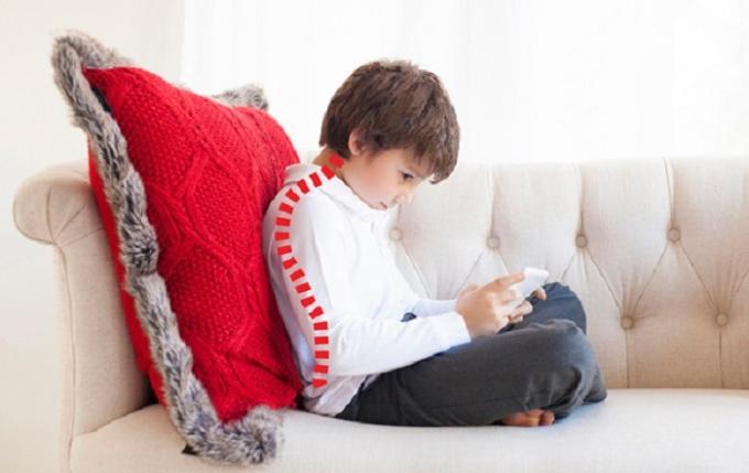 Cúi đầu xem điện thoại trong một thời gian dài cũng có thể gây chứng cong, vẹo cột sống ở trẻ. Ảnh minh họa.