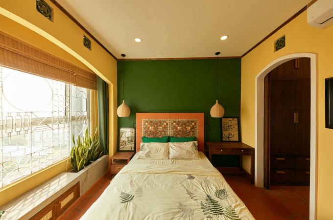 Trong phòng ngủ, giường làm từ gạch tàu và gỗ, đầu giường có ốp tấm mosaic gốm. Sau cửa kính, nhóm thiết kế bố trí thêm hệ song sắt để tăng cảm giác về một căn nhà Việt. Ảnh: Thiết Vũ.