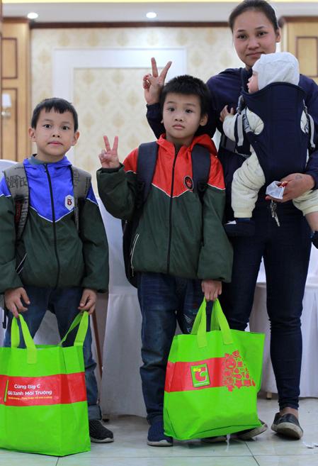 Một gia đình mưu sinh bằng việc bán hàng rong trên phố cổ nhận quà Tết của Quỹ Hy Vọng. Ảnh: Phan Dương.