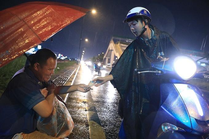 Ông Bùi Hữu Minh bị mù từ năm 7 tuổi, hàng ngày, từ Gò Vấp, ông đi bán vé số từ 6 giờ sáng tới khuya. Nắng nóng tuy mệt chút nhưng bán được vé số, chứ trời mưa là ế vì khách ngại dừng lại mua. Người ướt thế nào không cần thiết nhưng mưa nhất thiết phải ôm vé số trong lòng, không bị giang hồ giật, ông Minh nói. Ảnh: Hữu Khoa.