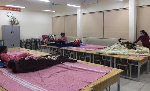 23h30 ngày 30/1, các phụ huynh, học sinh lớp 3E trường tiểu học Xuân Phương kê bàn ghế thành bốn giường để nghỉ ngơi và sinh hoạt. Ảnh: Nhân vật cung cấp.