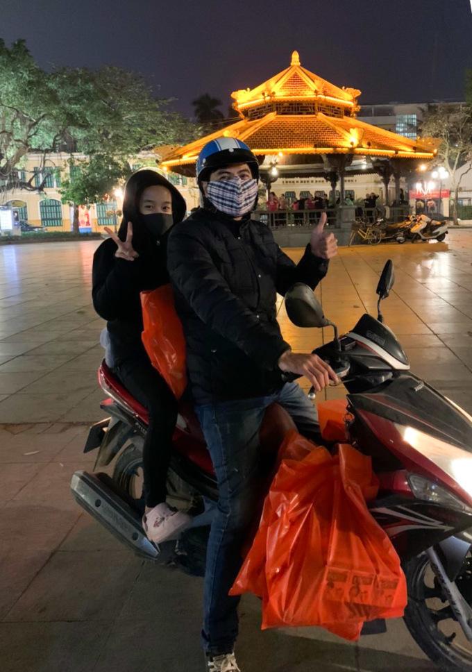 Bé Nguyệt Anh cùng bố đi tặng quà cho người vô gia cư trong đêm. Ảnh: Thanh Hiển.