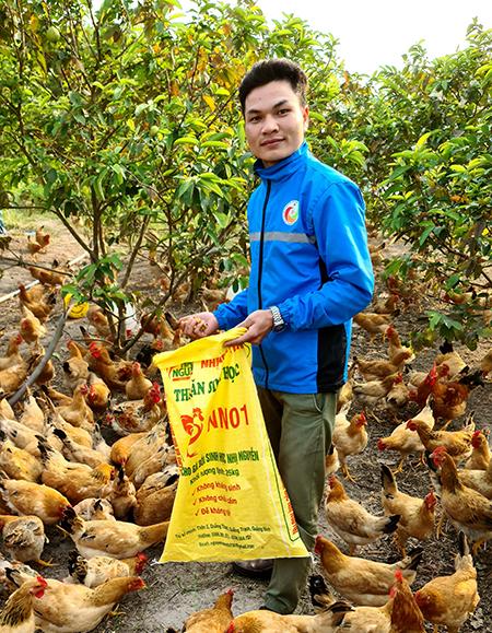 Nguyễn Văn Nhị cho đàn gà cám vi sinh vật do chính anh nghiên cứu và sản xuất. Ảnh:Nhân vật cung cấp.