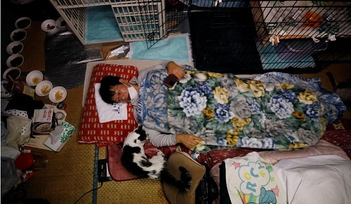 Sakae Kato nằm trên giường bên cạnh Charm, một con mèo ông đã cứu cách đây 5 năm bị nhiễm virus bệnh bạch cầu ở mèo, tại nhà của ông ở Namie, tỉnh Fukushima, Nhật Bản, ngày 20/ 2/ 2021. Ảnh: Reuters.